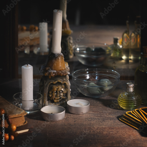 Fotografia Burning candles, fortune-telling cards and tincture bottles are reflected in an