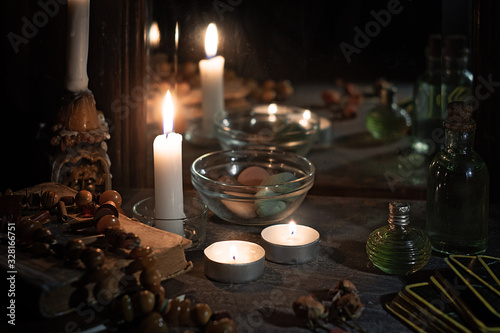 Burning candles, fortune-telling cards and tincture bottles are reflected in an Billede på lærred