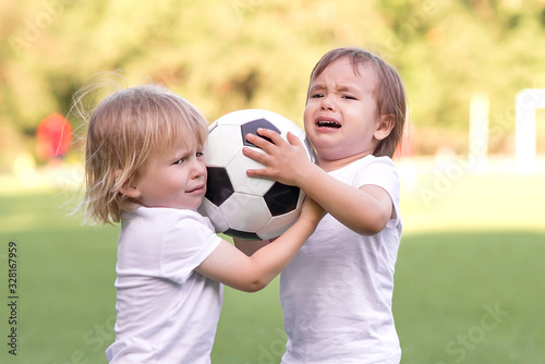 Two little toddlers arguing at football field or playground over soccer ball trying to take or grab ball Wallpaper Mural