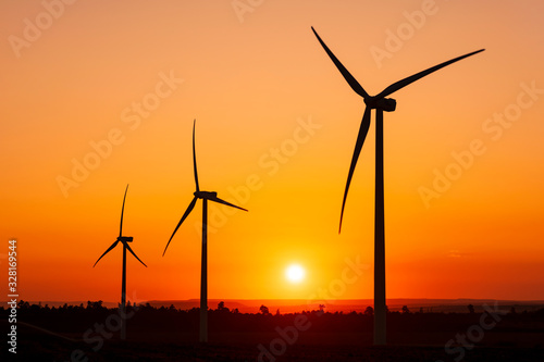 Photo Large wind turbines with blades in field on sky background with bright orange sunset