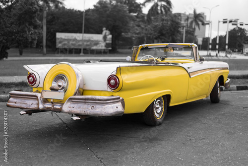 Obraz colorkey of yellow and white old american classic car with fin tails in havana - fototapety do salonu