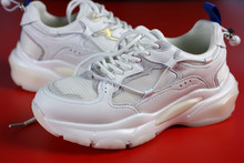 A Pair Of White Women's Sneakers On A Red Background
