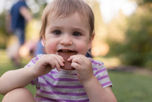 A Toddler Is Enjoying A Snack Outside In The Summer Time.
