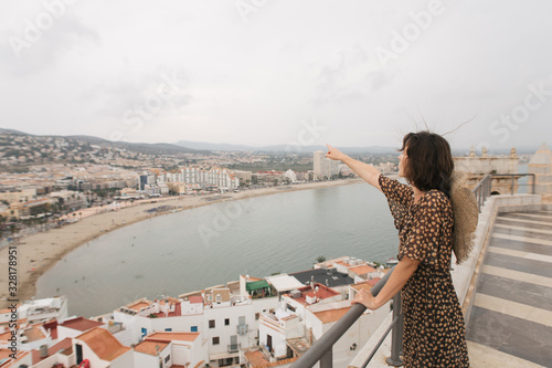 Foto young female traveler stands on top of castle, city view, Peniscola Spain