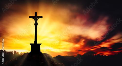 Obraz na plátně Cross with Christ on the top of the rocky mountain at sunset