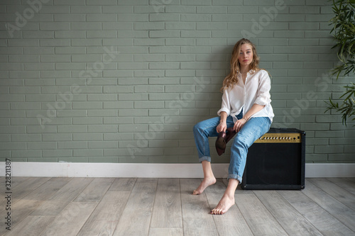 Young beautiful woman sitting on subwoofer with bare feet next to green plant Canvas-taulu