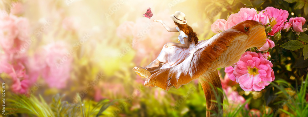Fototapeta Elf woman in dress and hat sitting on fantasy giant large mushroom releasing butterfly from hand in magical enchanted fairy tale rose flower blooming garden, fairytale floral fabulous background
