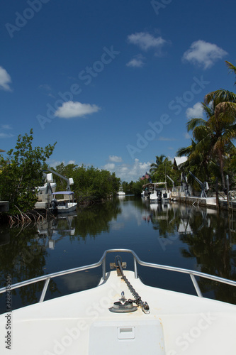 Boats line a residential waterway in South Florida on a calm sunny day.