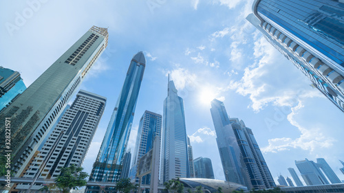 Obraz Looking up to high-rise office buildings, skyscrapers, architectures in financial district with blue sky. Smart urban city for business and technology concept background in Downtown Dubai, UAE. - fototapety do salonu