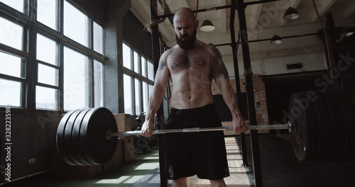 Fototapeta Strong athletic young bearded Caucasian man lifting heavy barbell in large hardcore gym hall