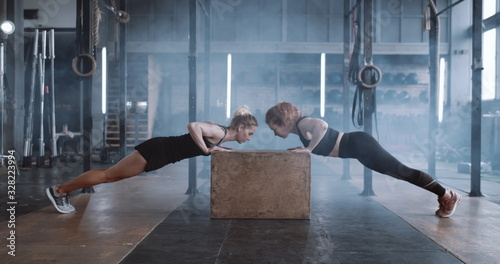Photo Side view happy attractive young blonde woman working out with personal female coach in gym doing push-ups slow motion