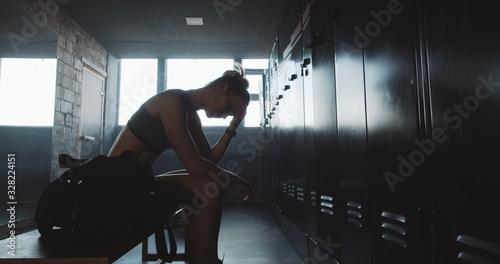 Fototapeta Sad sporty Caucasian woman sitting alone in dark gym locker room, feeling lost and upset overcoming failure slow motion. obraz