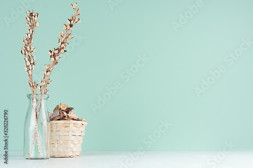 Obraz Home decorations in eco style - beige wooden wicker basket, dried plant and flowers, glass bottle in green mint menthe interior on white wood board. - fototapety do salonu