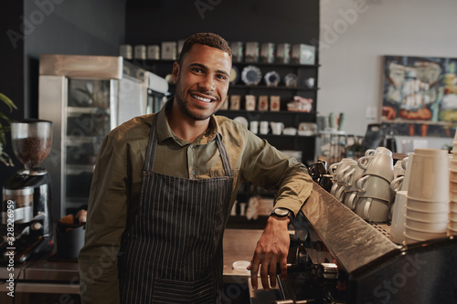 Foto Portrait of young afro-american male business owner behind the counter of a coff