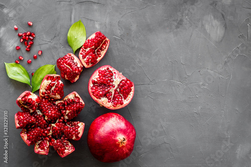 Ripe pomegranate fruit near leaf on grey background top-down copy space