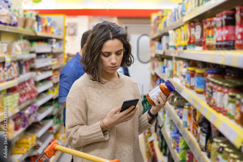 Fototapeta Focused woman using smartphone in grocery store. Young woman reading checklist via smartphone and choosing products in grocery store. Supermarket concept obraz