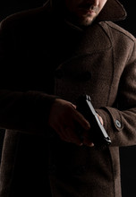A Man In A Dark Coat Holds A G...