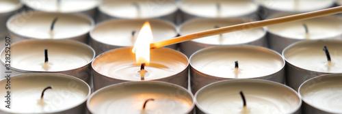 Obraz na plátně One burning candle and many extinguished candles, banner.