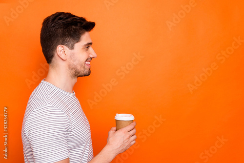 Just for you. Profile photo of funny attractive macho guy hold hand hot takeout coffee beverage look side empty space wear striped t-shirt isolated vivid orange color background