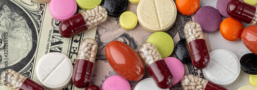 The concept of making money on medicines. Multicolored drugs on a background of dollars. Different remedy, pills, capsule, antibiotic and vitamin, panoramic banner.