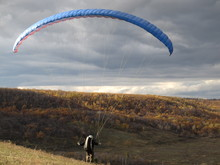 Paraglider Preparing To Jump Against The Autumn Forest