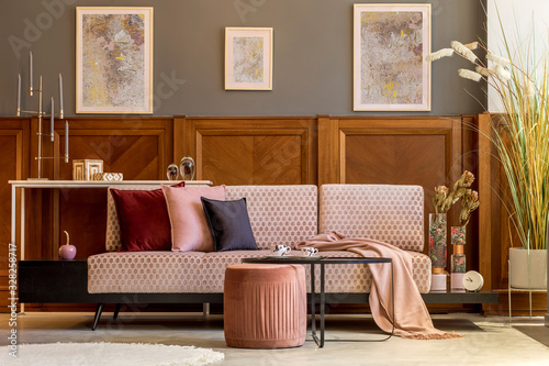 Obraz na plátně Interior design of living room with stylish velvet sofa, elegant pouf, coffee table, plants, pillows, decoration, mock up posters and elegant personal accessories
