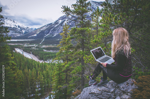 Fotografia, Obraz Digital nomad woman working on her laptop in the mountains