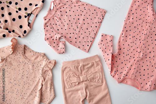 babyhood and clothing concept - pink clothes for baby girl with dot print on whi Canvas Print