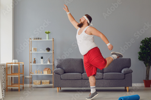 Foto Funny red fat man doing exercises while standing at home.