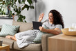 canvas print picture - technology, leisure and people concept - happy smiling woman with tablet pc computer having video chat and waving hand at home
