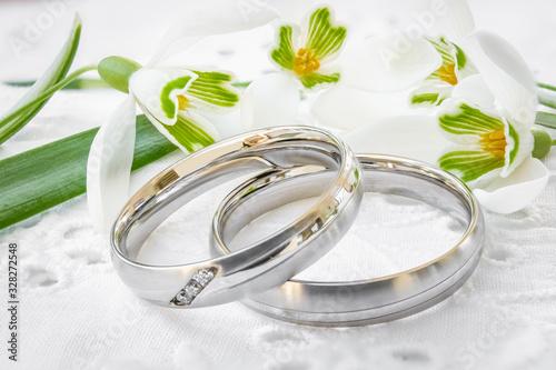 Fototapeta Frühlingsgefühle - Silberne Eheringe liegen auf weißer Spitze neben frischen Sch
