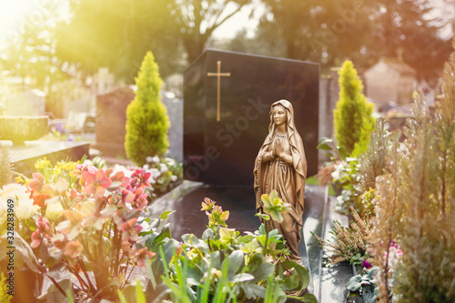 Virgin Mary at cemetery, graveyard background, tombstone, sunlight tone Wallpaper Mural