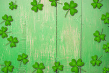 Shamrocks On Green Wooden Table A Symbol Og St. Patricks Day. Bbanner With Corner Border Of Shamrocks.Textured Pattern.