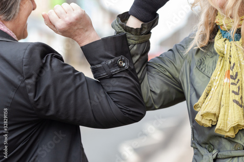 Obraz Elbow bump. New novel greeting to avoid the spread of coronavirus. Two women friends meet in a British street and instead of greeting with a hug or handshake, they bump elbows instead. - fototapety do salonu