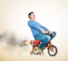 Cool Man In Casual Wear Rides A Children's Bike With Alternative Rocket Engine. On A Light Yellow Background.