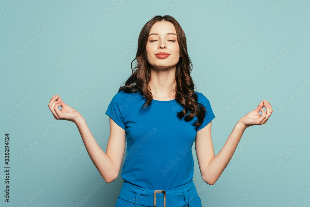 Fototapeta smiling girl standing in meditation pose with closed eyes on blue background