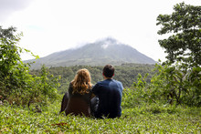 Back Of Young Couple Looking At Arenal Volcano, Sitting On Green Grass And Enyojing Nature, Costa Rica, Central America, La Fortuna