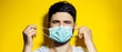 Close-up portrait of young man, takes off the medical protective flu mask, on background of yellow color.