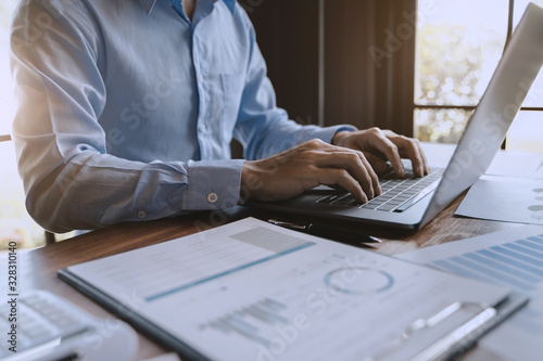 Fototapety, obrazy: Accountant working with laptop computer and paper work calculating a value numbers.