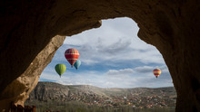 Landscape Of Cappadocia With Balloons. Cavetown And Monastery Selime In A Stone Frame Of Ancient Cave. Colored Hot Air Balloons Fly Of Over The Mountain Valley - View Through The Window Hole.