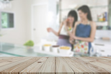 Beautiful Pattern Of Empty Brown Plank Wooden Board As Mock-up Display Shelf Or Tabletop With Blurred People Activity Of Two Women As Mom And Daughter Enjoy For Cooking In A Clean Kitchen Background.