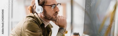 Side view of pensive 3d artist in headphones looking at computer monitor, panora Fototapeta