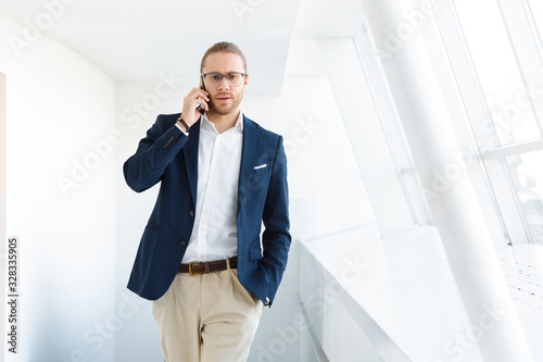 Fototapety, obrazy: Concentrated young businessman indoors in office