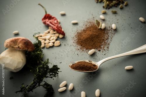 Photo Spezie e fagioli su fondo grigio neutro con erbe e peperoncino