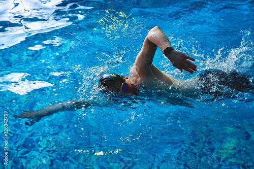 Fotografia Professional male swimmer crawls underwater in a blue swimming pool