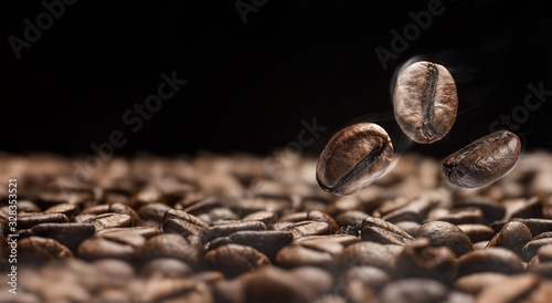 Fototapeta roasted coffee close-up on a dark background of other coffee beans obraz