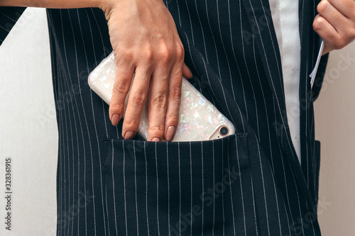 Photo Business lady puts phone in jacket pocket.