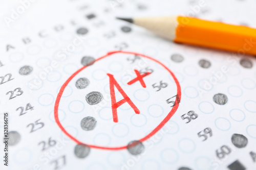 Test score sheet with answers, grade A+ and pencil, close up Fototapeta