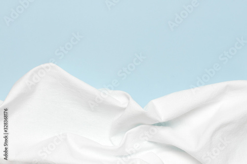 Vászonkép White crumpled natural cotton fabric on delicate blue background top view flat lay with copy space
