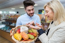 Attentive Retailer Showing Basket Of Produce To Customer